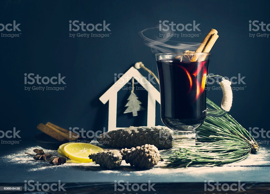 Glass hot Mulled wine with sticks of cinnamon, anise, lemon stock photo