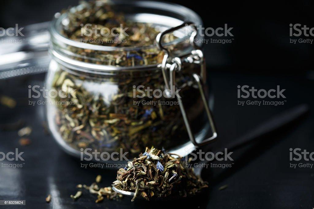 Glass jar full of green tea leaves stock photo
