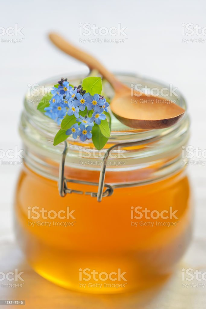 glass jar full of honey stock photo