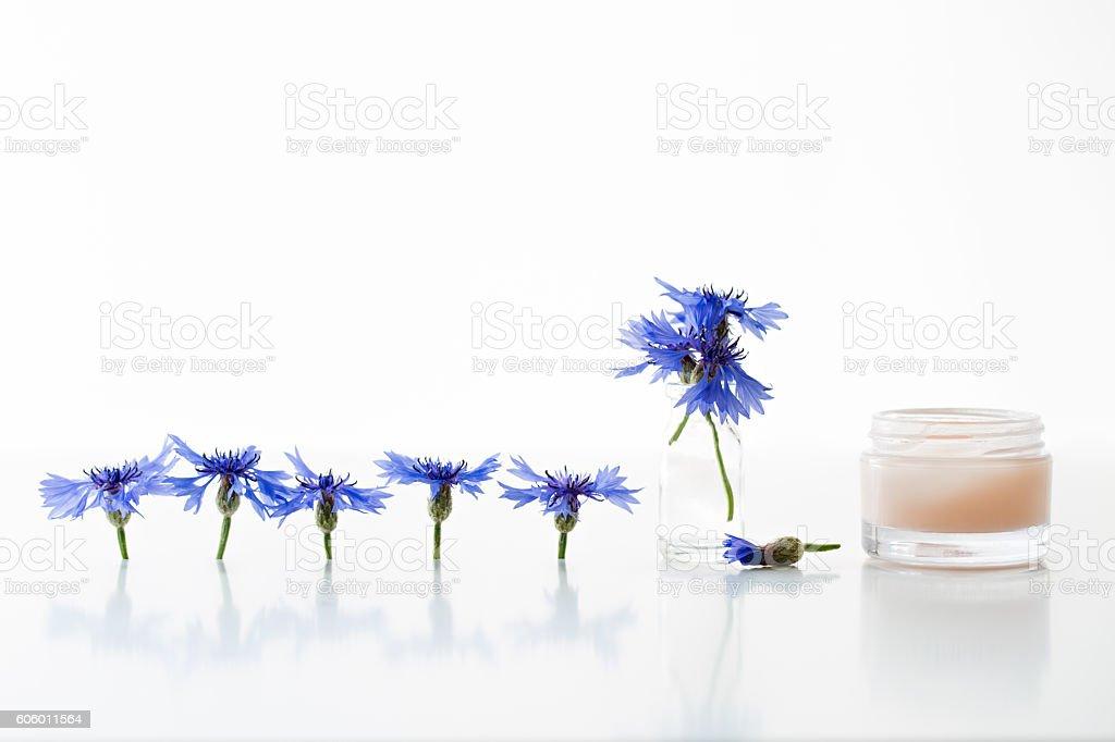 Glass jar of beauty cream and cornflowers stock photo