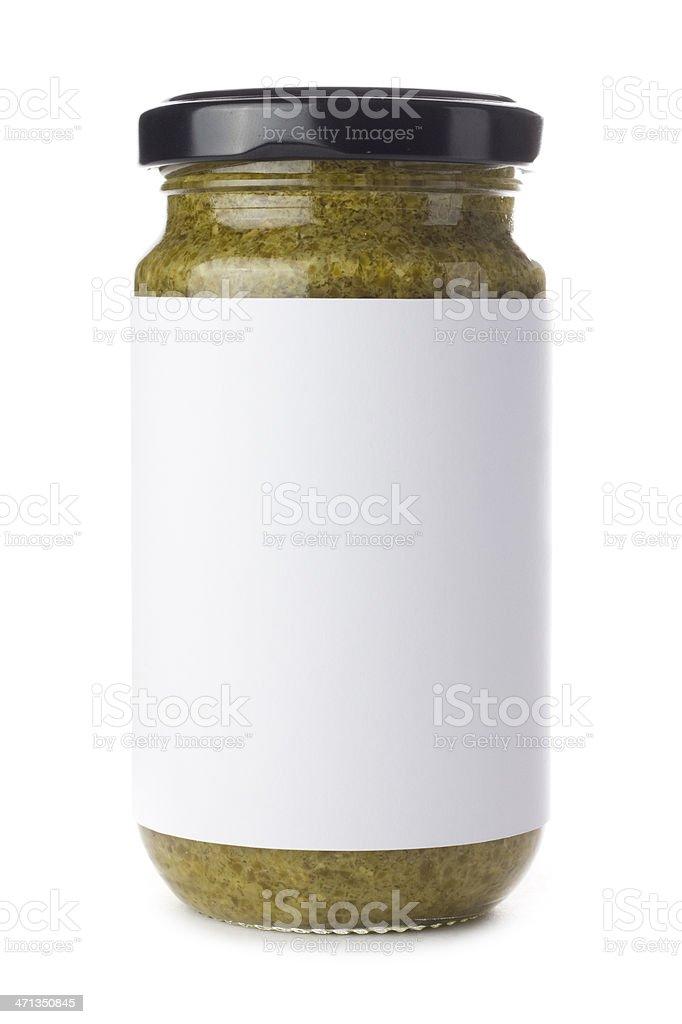 Glass jar of green pesto on a white background stock photo