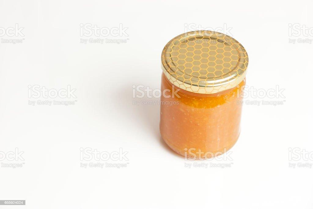 Glass jar of honey on white background stock photo