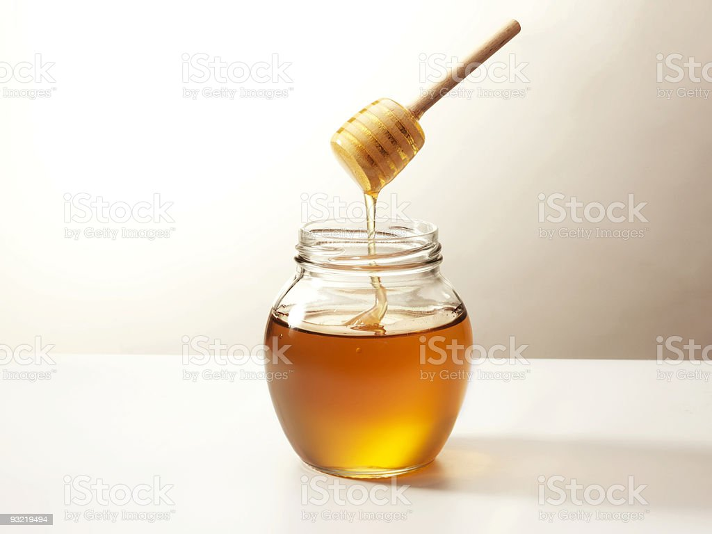 Glass jar of honey ready to be severed stock photo