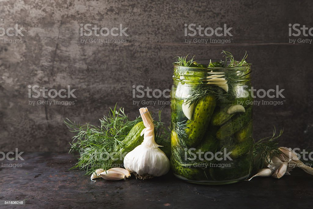 Glass jar of pickles with dill and garlic stock photo