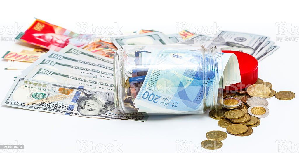 glass jar of pile of  Israeli Shekels banknotes and  dollars stock photo