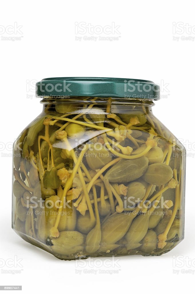 Glass jar of preserved caper buds (vertical closeup) royalty-free stock photo