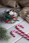 Glass jar with Christmas cookies and candy canes.
