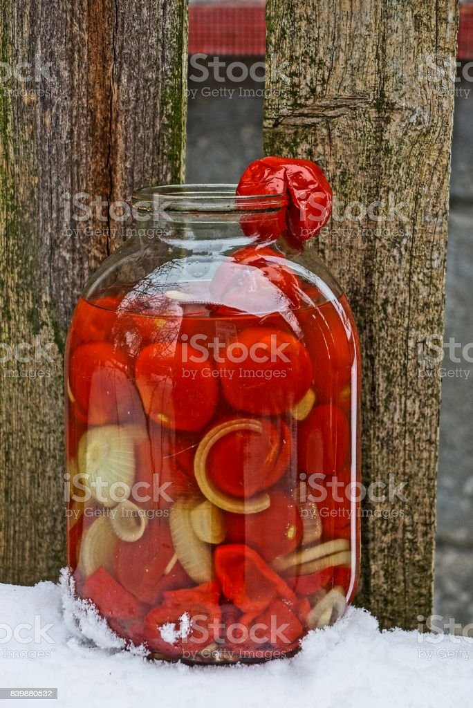 glass jar with sour tomatoes outdoors in the snow stock photo