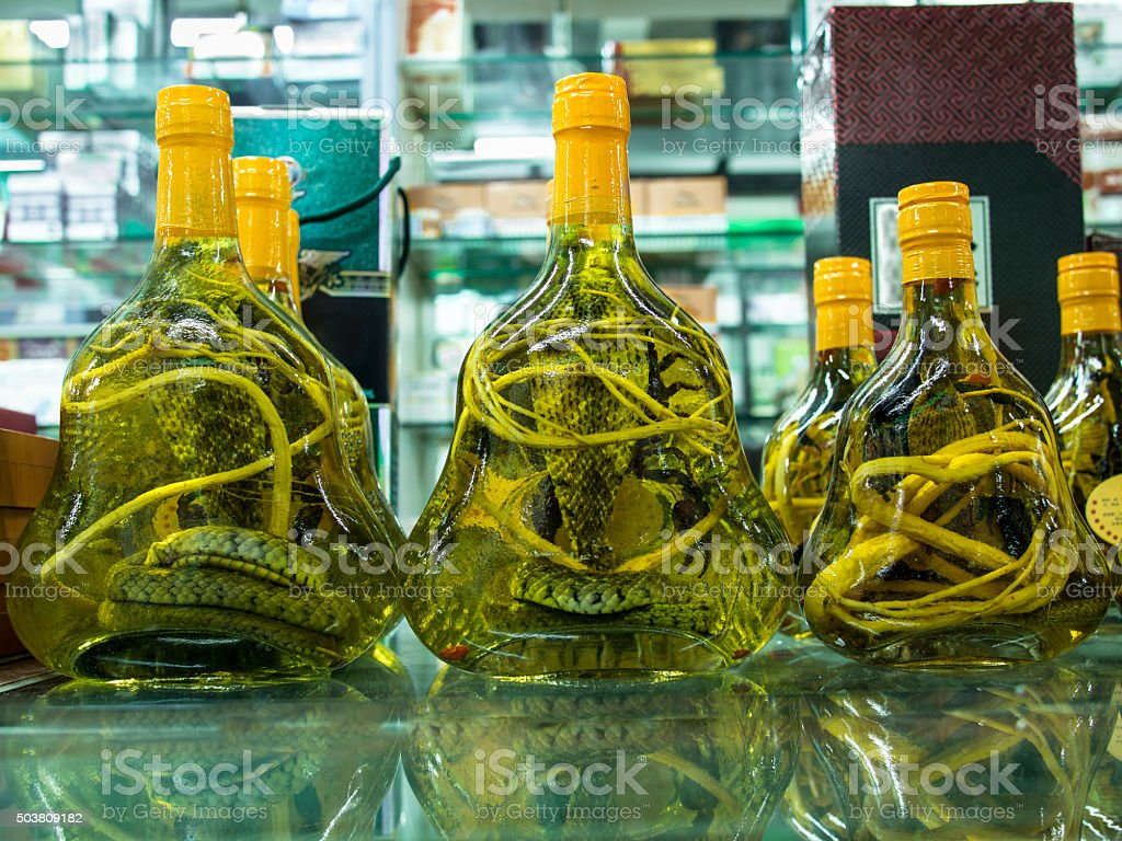 Glass jars with alcoholized snakes are on a glass table stock photo