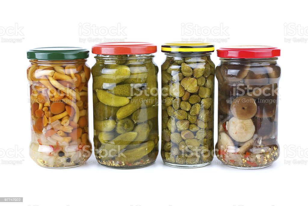 Glass jars with marinated cornichons, mushrooms and capers stock photo