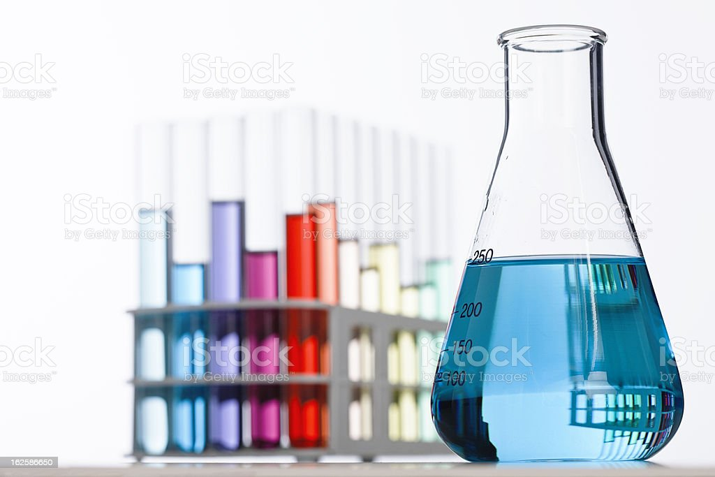 Glass lab flask in front of multicolored test tubes stock photo