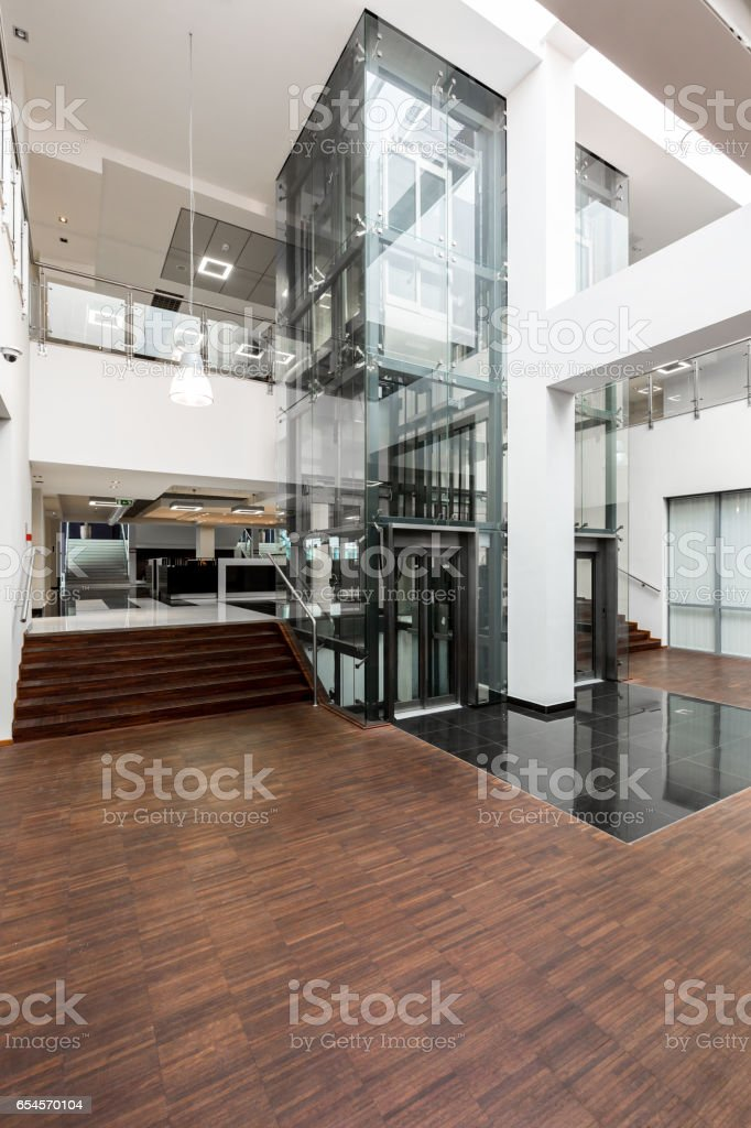 Glass lift and wooden stairs in lobby stock photo