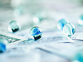 Glass marbles on paper currency
