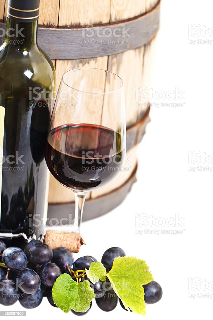 Glass of a red wine, bottle, barrel and grapes stock photo
