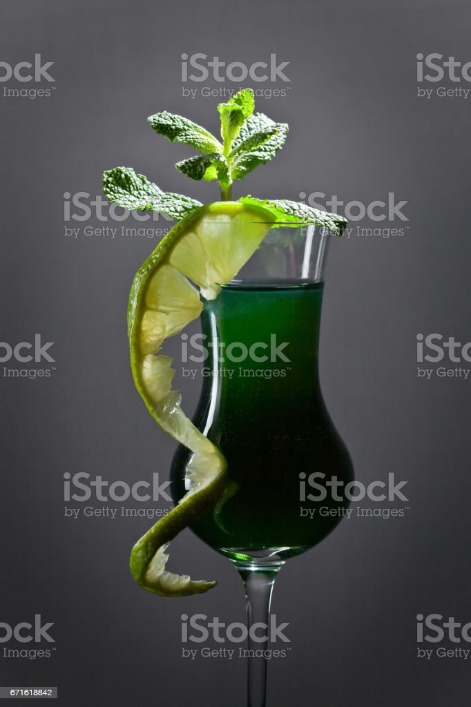 Glass of absinthe garnished with lime and mint leaves stock photo