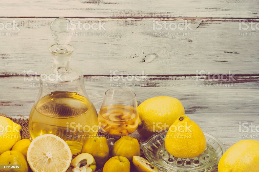 Glass of alcohol tincture made from quince and lemon fruits, liquor in a bottle on rustic background stock photo