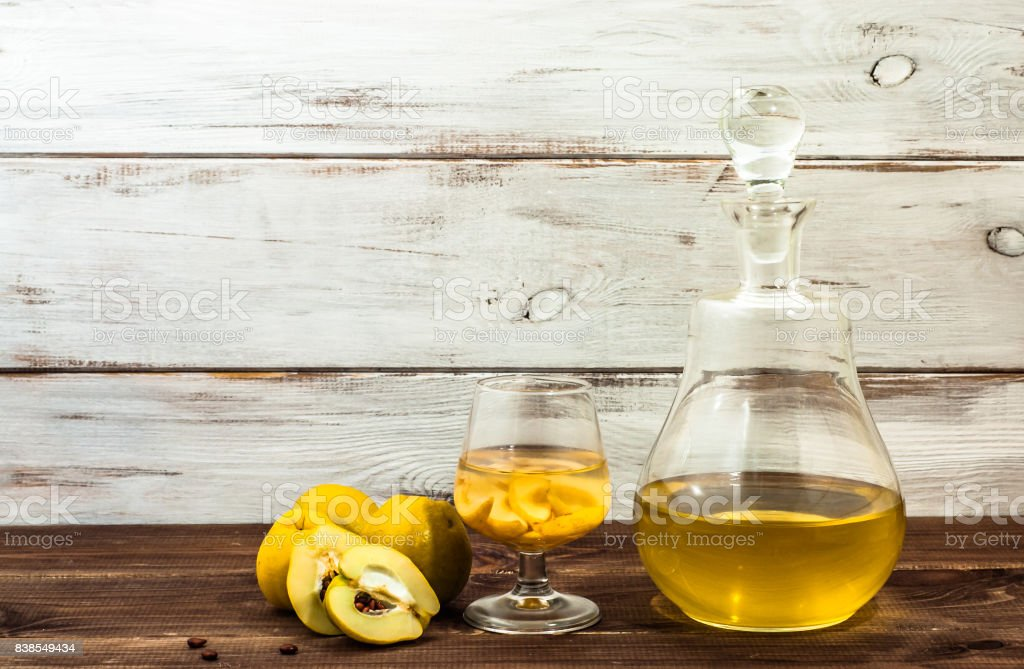 Glass of alcohol tincture made from quince fruit, liquor in a bottle on rustic background stock photo