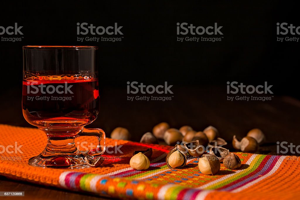 Glass of alcoholic punch drink and hazelnuts stock photo