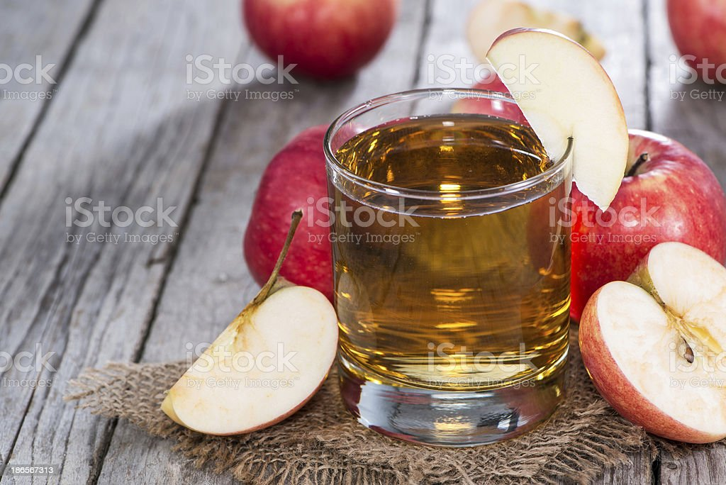 Glass of apple cider surrounded by freshly-cut apples stock photo
