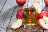 Glass of apple cider surrounded by freshly-cut apples