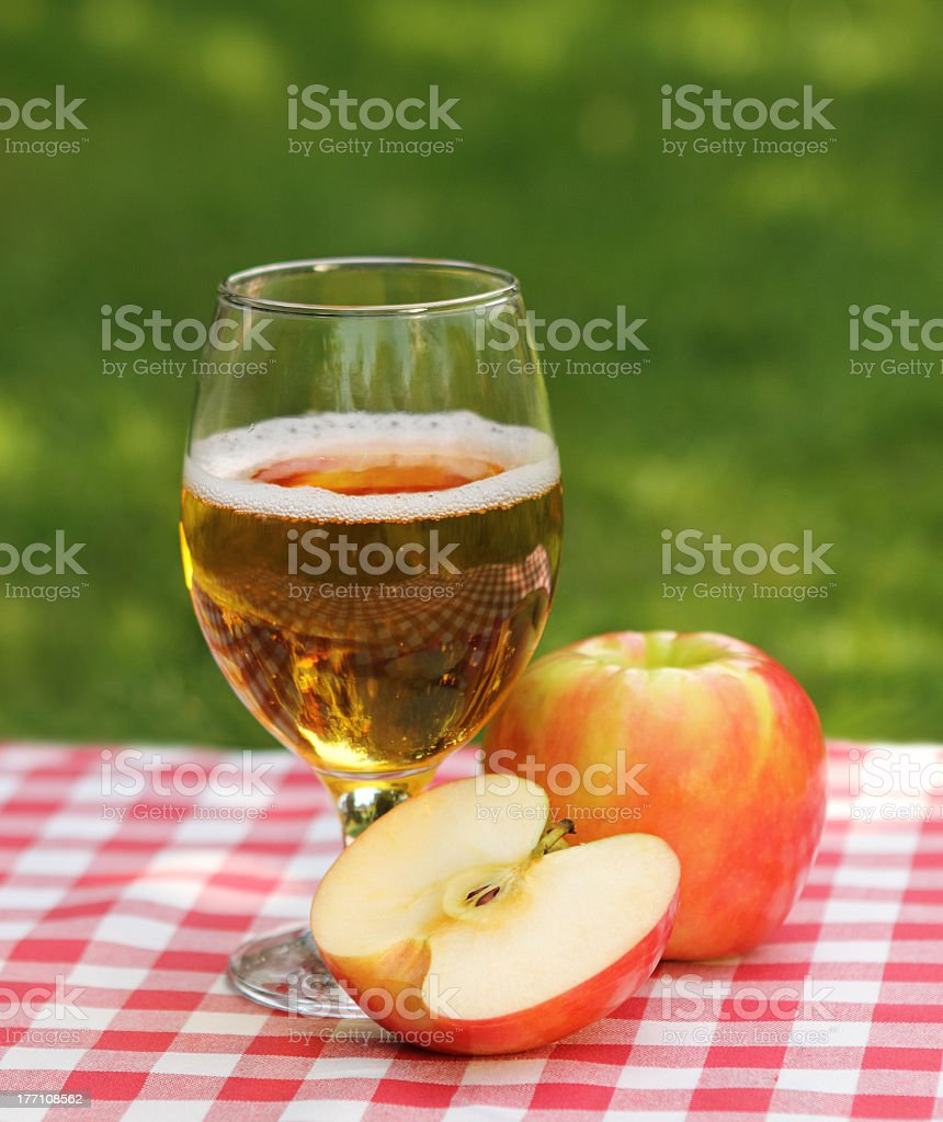 A glass of apple juice and one and a half apples on a table stock photo
