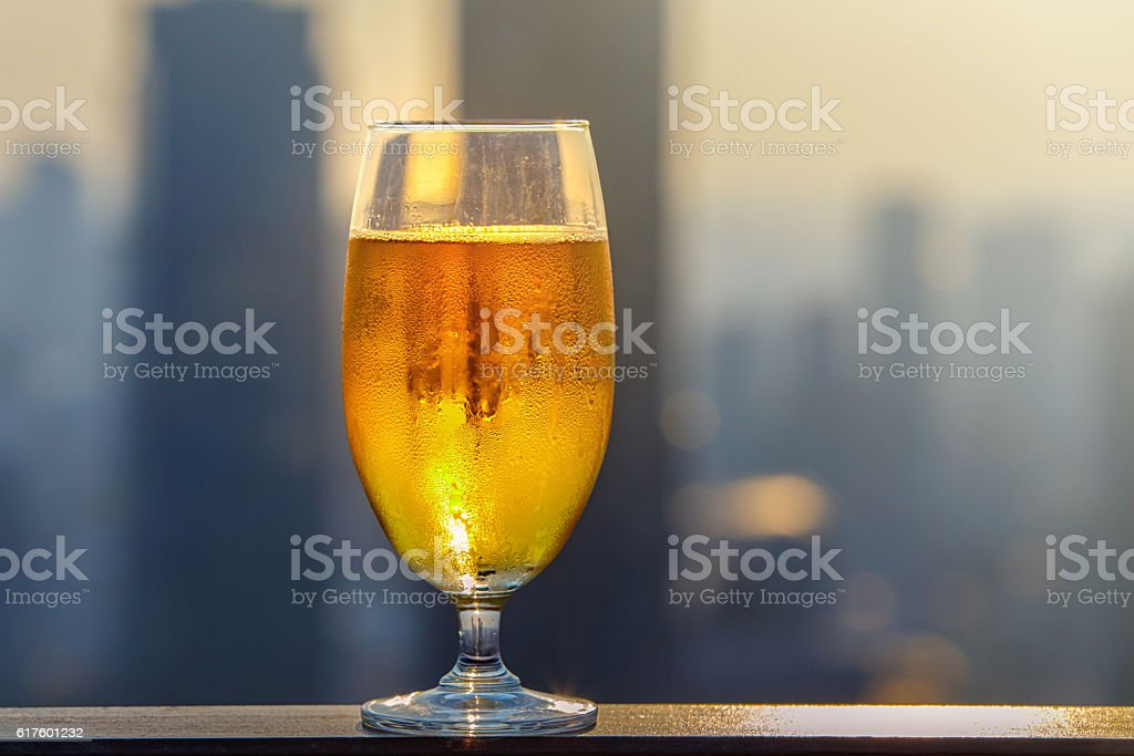 Glass of beer against blurred asian city stock photo