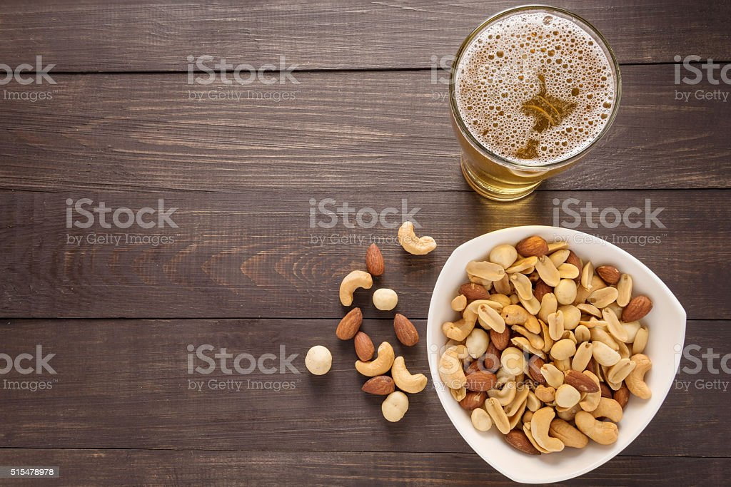Glass of beer and almond, macadamia, peanut, cashew nut stock photo