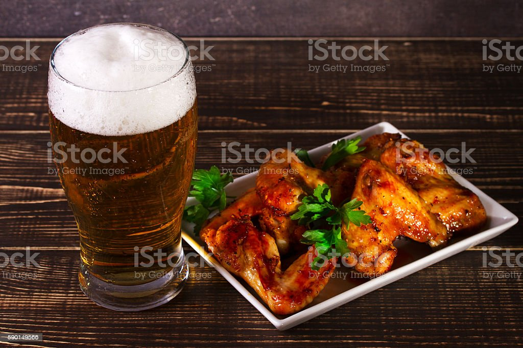 Glass of beer and chicken wings on dark wooden background stock photo