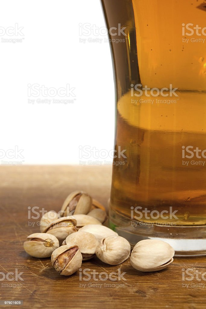 glass of beer and pistachios at a wooden table royalty-free stock photo