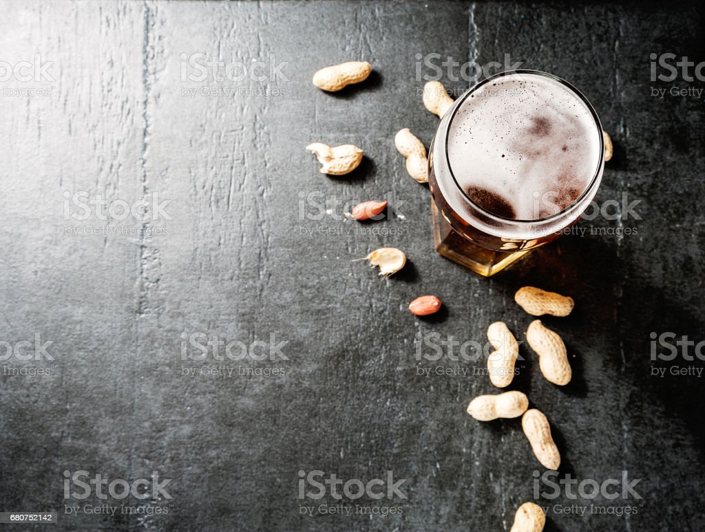 Glass of beer and snack of peanuts on a concrete table stock photo