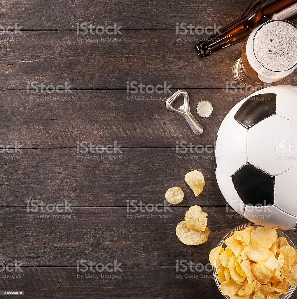 glass of beer and soccer ball. wooden space for text stock photo