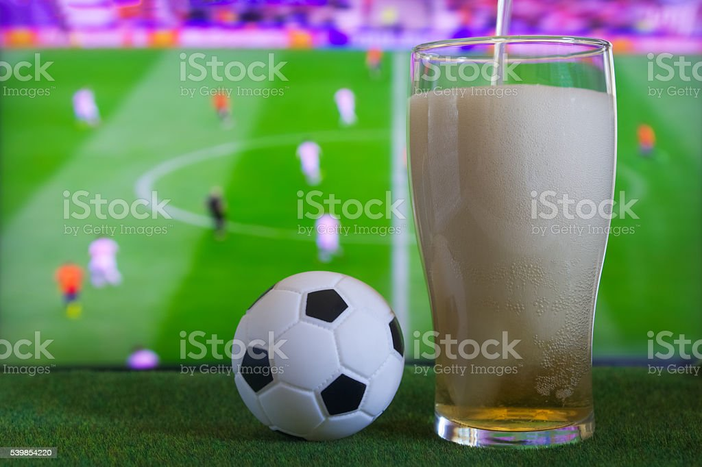 Glass of beer and tv, football match in background stock photo