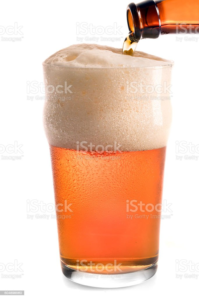 Glass of Beer Being Poured, Isolated on White stock photo