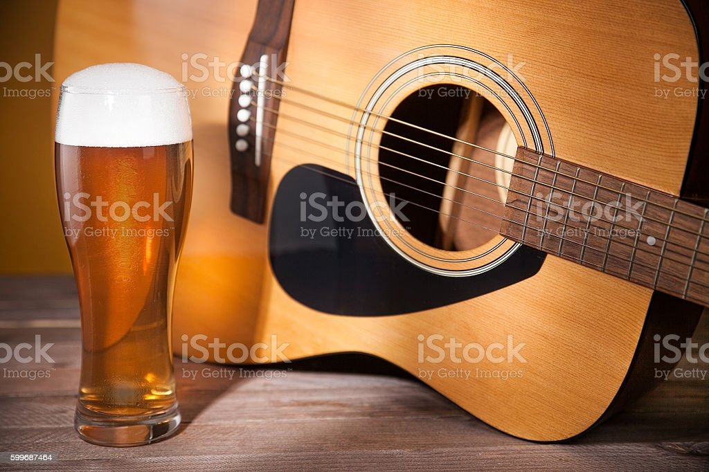 glass of beer near acoustic guitar. stock photo
