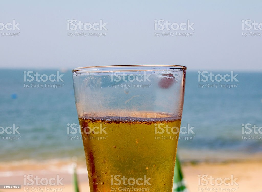 Glass of beer on a blurry background of a beach stock photo