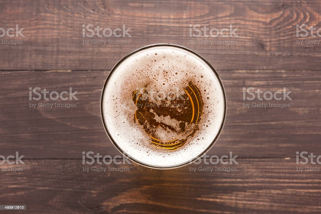 glass of beer on a wooden background. Top view stock photo