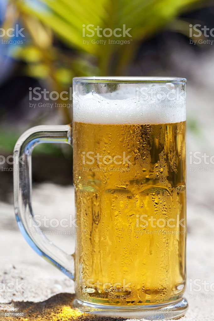 Glass of beer on beach stock photo