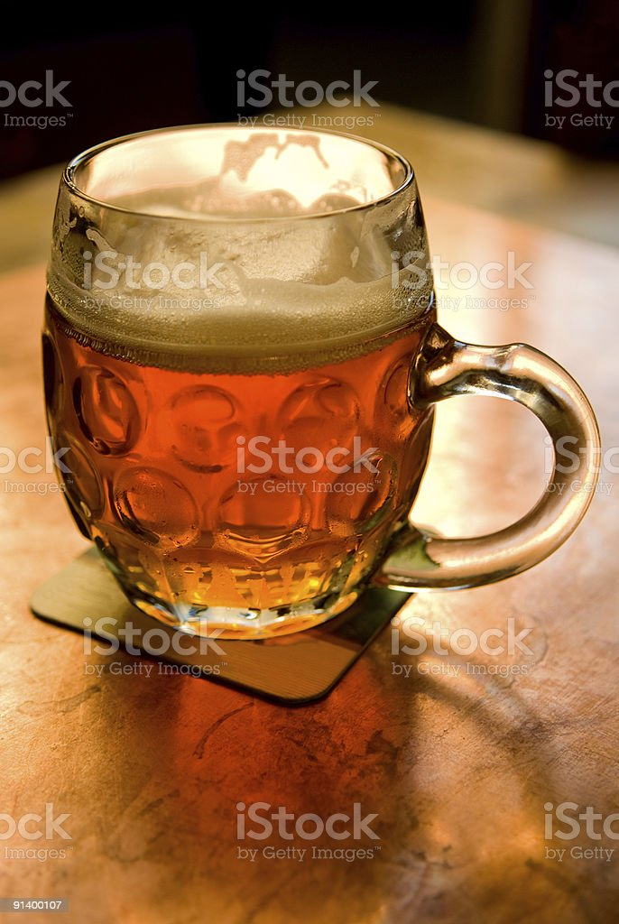 Glass of beer on table in pub. stock photo