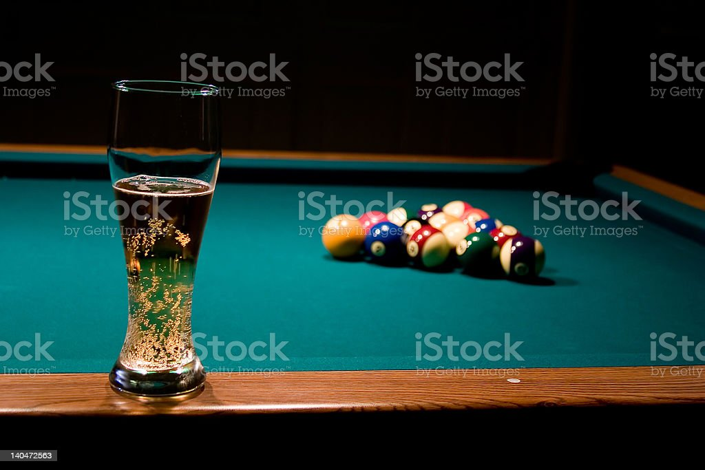 Glass of beer on the pool table stock photo