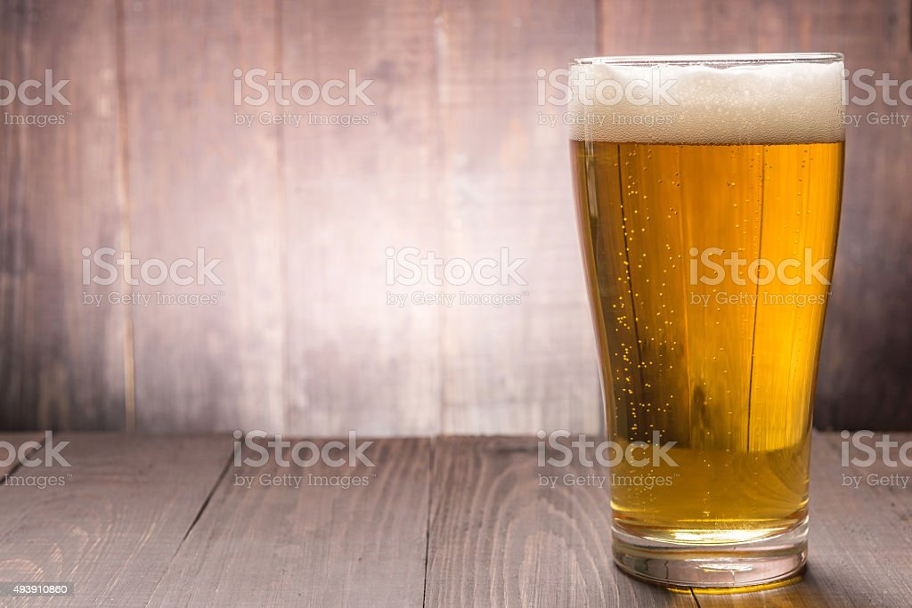 Glass of beer on the wooden backgorund stock photo