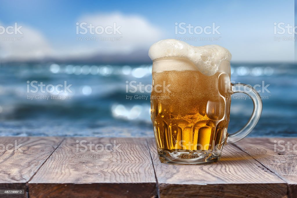 Glass of beer on wooden table with sea on background stock photo