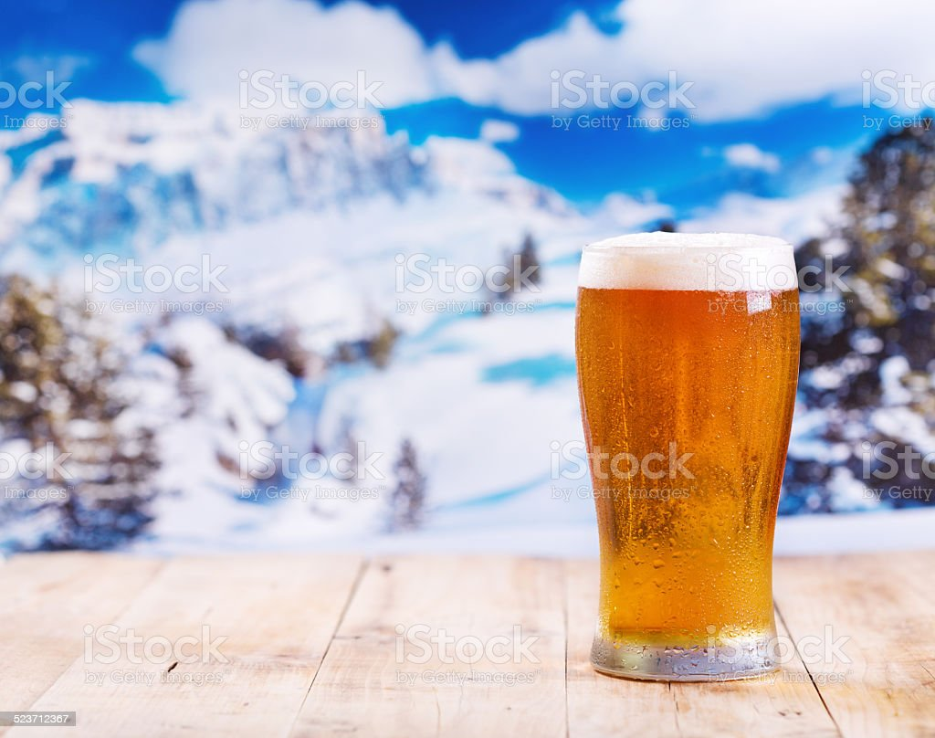 glass of beer over winter landscape stock photo