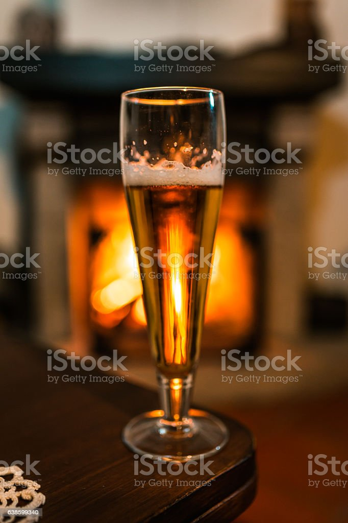 Glass of beer with fireplace on background stock photo