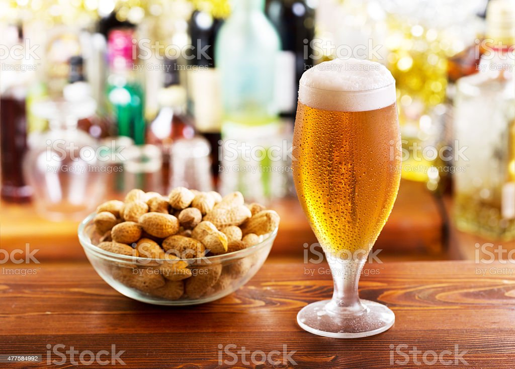 glass of beer with peanuts stock photo