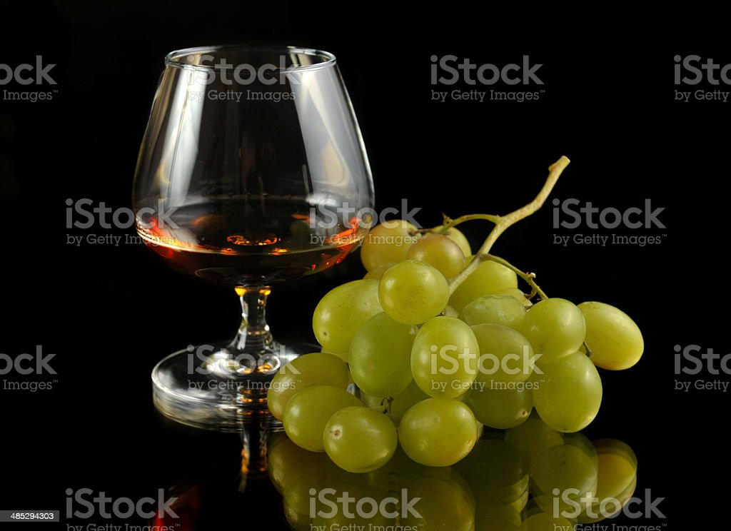 glass of brandy and grapes stock photo