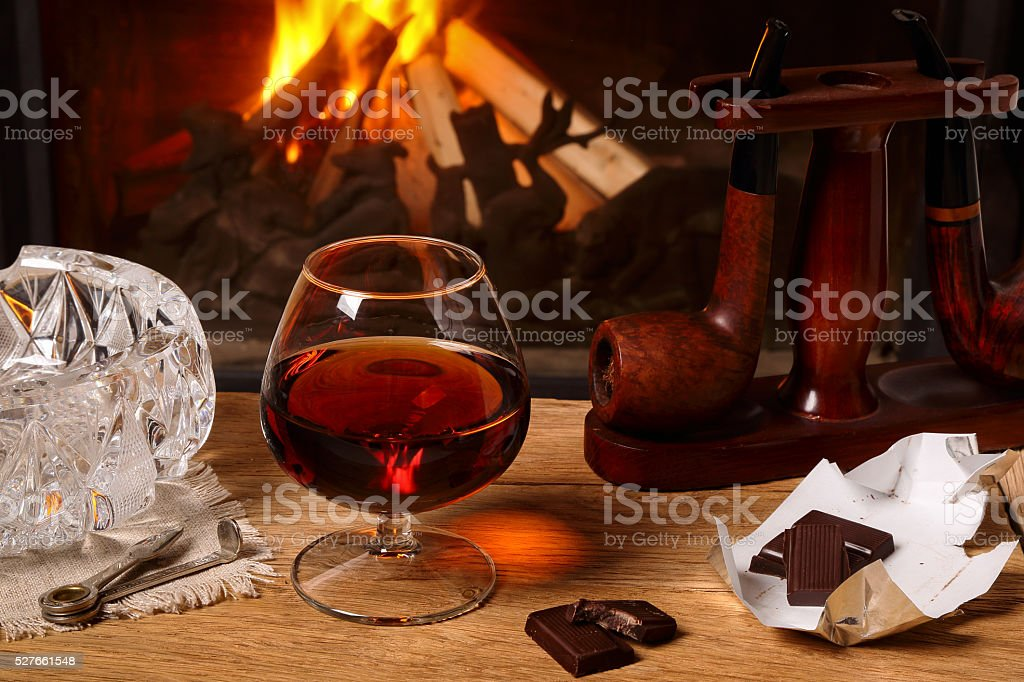 Glass of brandy, chocolate and tobacco pipes stock photo