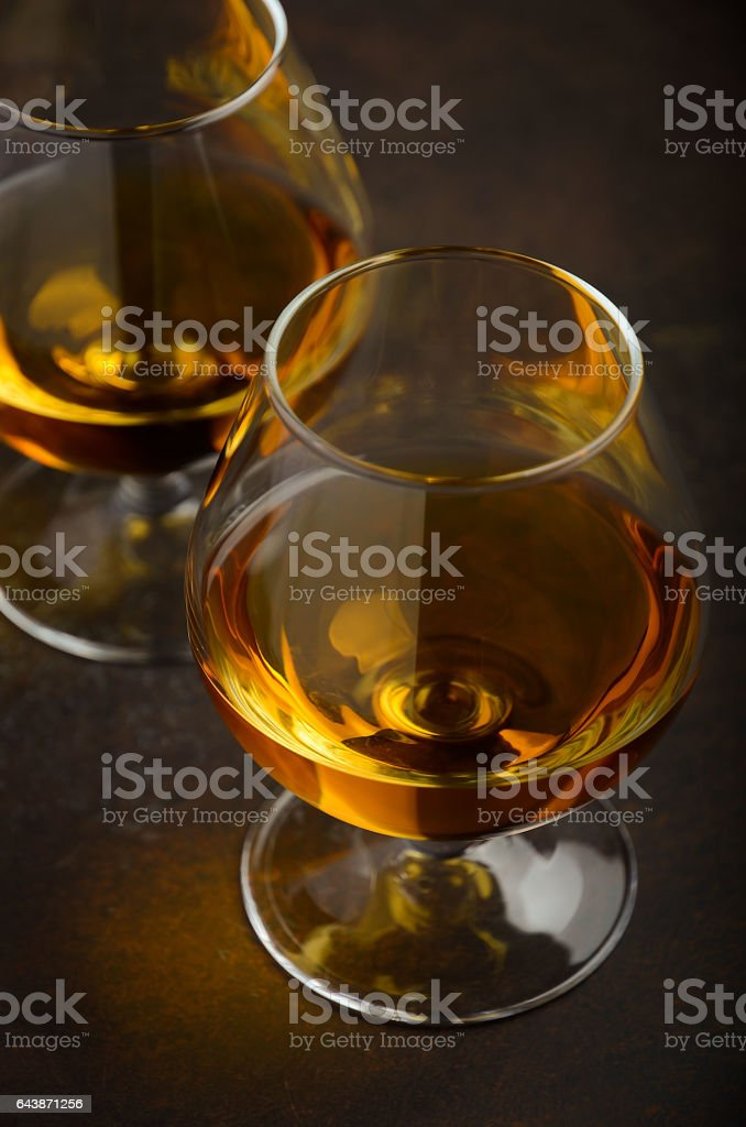 Glass of brandy or cognac on the old rusty background stock photo