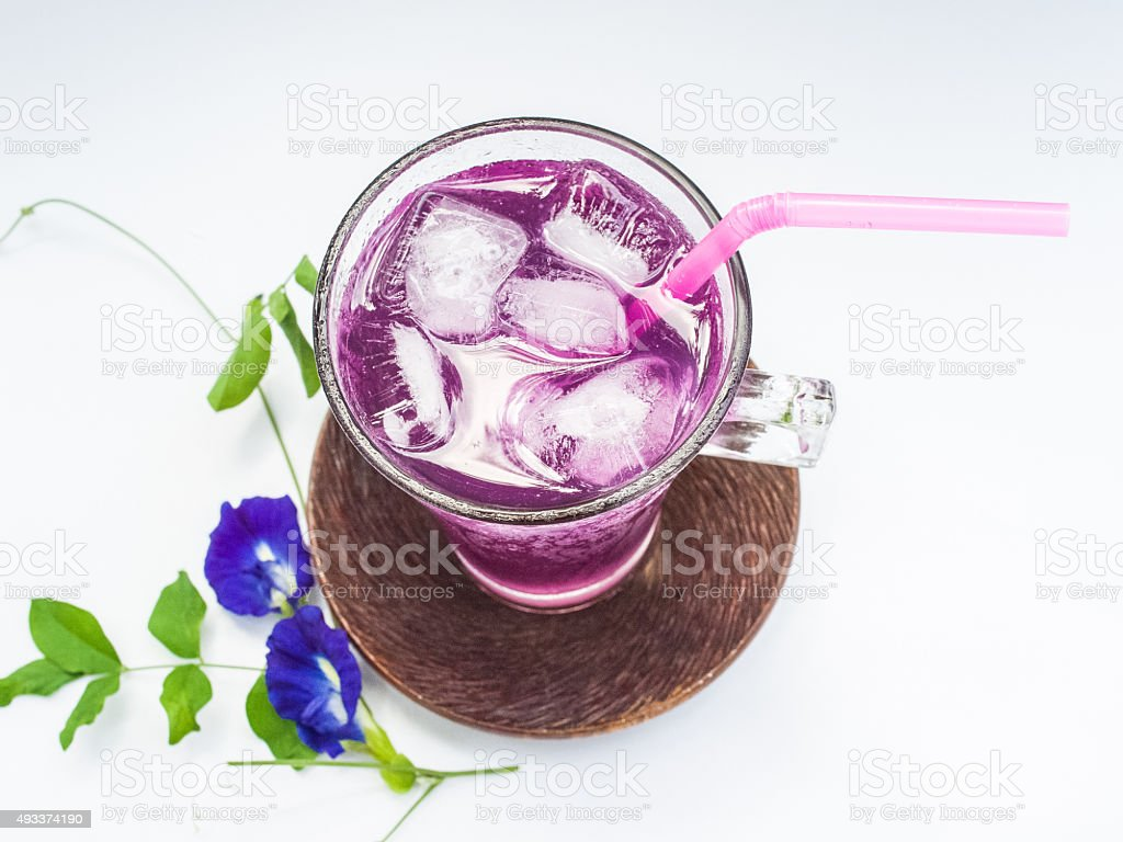 Glass of butterfly pea flower juice on white background stock photo
