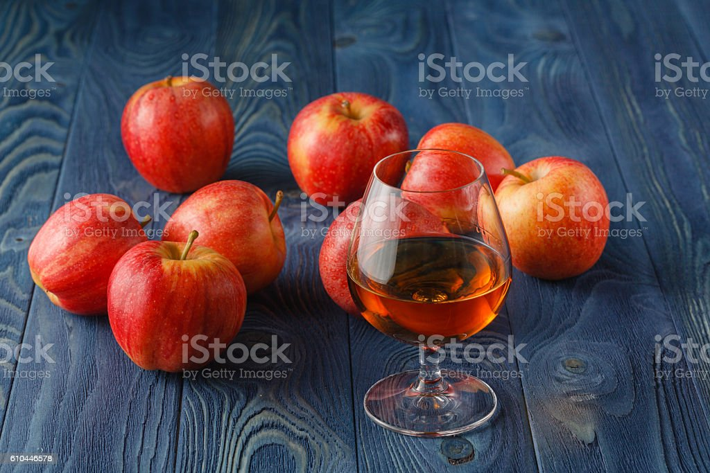 glass of Calvados Brandy and red apples stock photo
