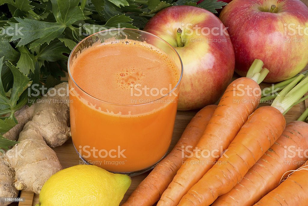 Glass of carrot juice with carrots apples lemon and ginger stock photo